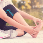 Young woman massaging her plantar fasciitis after exercising and running