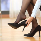 Businesswoman taking off high heeled shoes