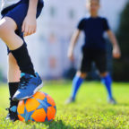 Two boys playing soccer with Osgood-Schlatters disease